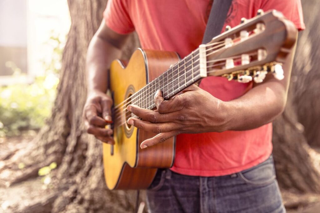立ってギターを弾く